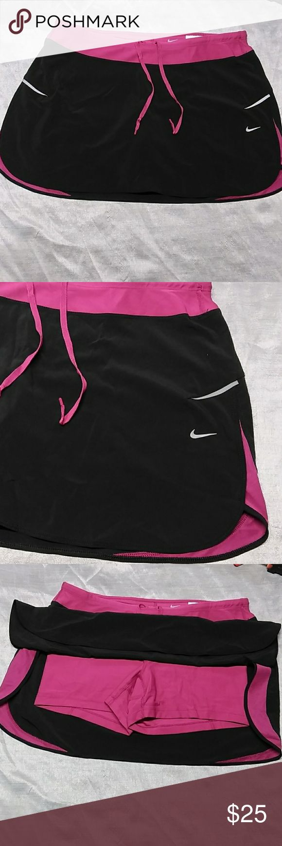 Nike Skirt Short S-7 Fri-fit Nike skirt short underneath  slits on both side color black and old rose.  Self tie on the waistline to adjust the fitting. Perfect condition   just like new.  Measurements laying flat  Waistline : 15. 5 inches Length:14 inches Pet/smooke Free home Nike Skirts