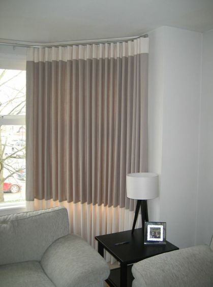 Contemporary, wave linen curtains fitted in a bay window with a top and bottom contrast band creating a simple and sophisticated look.