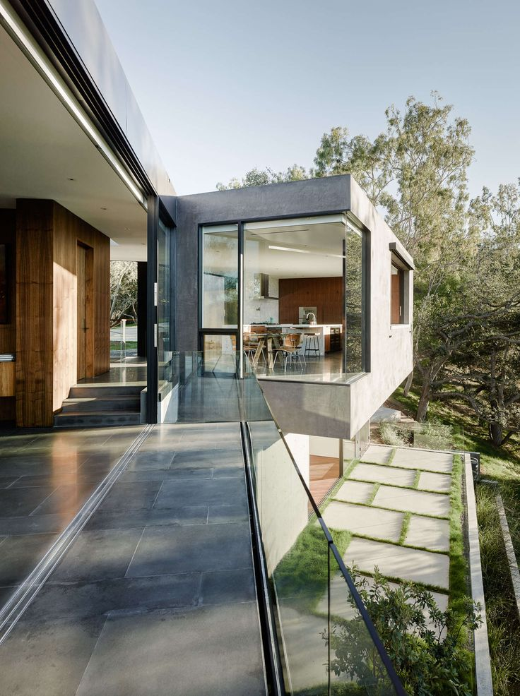 "The Oak Pass Main House uses an ""upside down"" program, with public spaces above the bedrooms, which are buried into the hill and beneath a green roof of edib..."