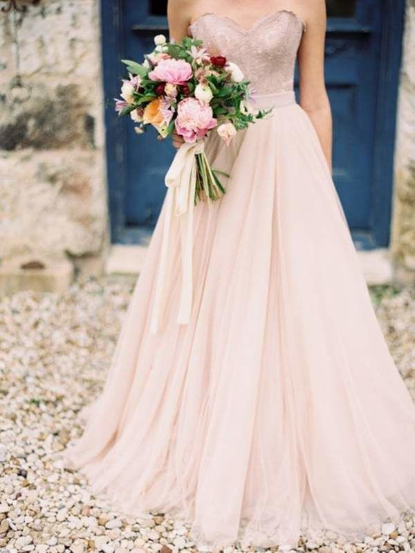 Blush is such a flirty color that it practically floats down the aisle. This sweetheart neckline wedding dress is made even sweeter with a bright bouquet tied with a long silk ribbon to complete the bridal look for a summer wedding.