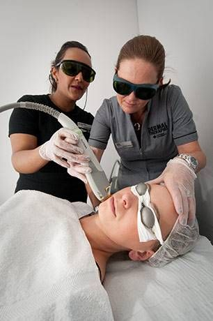 Two dermal therapy students apply treatment to a patient's face