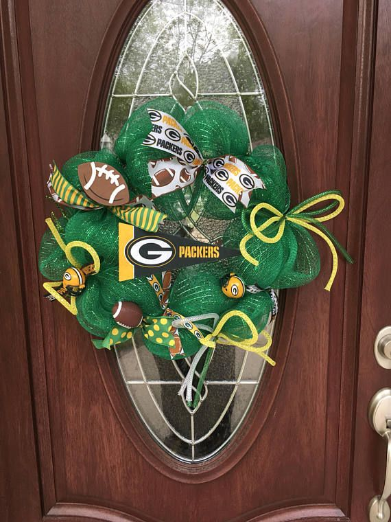 Green Bay Packer wreath done in green deco mesh. Embellishments include plastic 2 Green Bay Packer helmets, foam football, wooden football, deco tubing done in Green Bay Packer colors along with additional ribbon to accent your favorite team. Measures 25H x 23W *All of our products are sprayed with a preservative. This helps the product to keep their shape, prevents fraying, prevents fading from the sun and helps them last longer! *If buying multiple items, the shipping rate will be adjus...