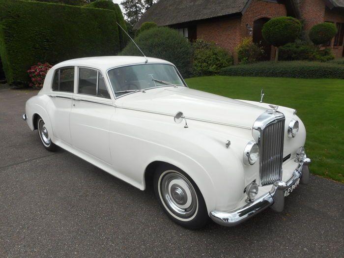 Bentley - S 1- 1957  Een mooie en goede Bentley S1 uit 1957. Hetzelfde model als de Rolls Royce Silver Cloud 1. Er zijn slechts 2927 stuks van deze statige auto gebouwd en deze is uitgevoerd in de kleur wit met de originele beige lederen bekleding. Het houtwerk is netjes het chroom is netjes de bekleding is netjes met de gebruikelijke gebruikssporen na 60 jaar en de carrosserie is netjes met enkele bijgewerkte plekjes maar keihard. De afgelezen stand is 25114 mijl. Er is de laatste jaren…
