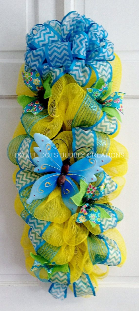 This is a 31 Yellow & Blue Butterfly Mesh Door Wall/Swag Mesh Wreath, accented with lime green ribbon, chevron ribbon and a tin butterfly on a pine
