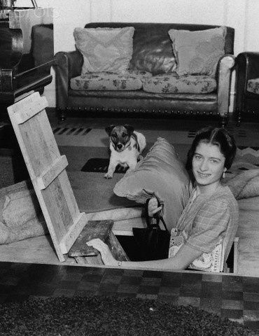 A woman emerges from an air raid shelter built underneath a sitting room of a house in Palmers Green, London, 1940.