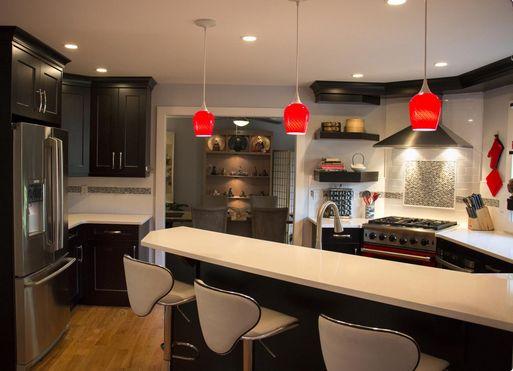 Dark smoke cabinets in this transitional kitchen. Love the red hanging lights. #interiordesign #homedecor