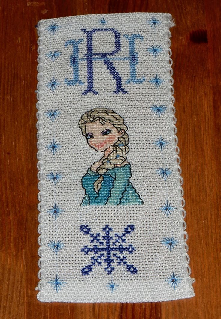 Een zelfgemaakte bladwijzer met borduurwerk in kruissteek met een monogram en Elsa uit Frozen.