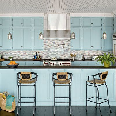 Stainless steel appliances and dark surfaces contrast perfectly with pale blue cabinets.