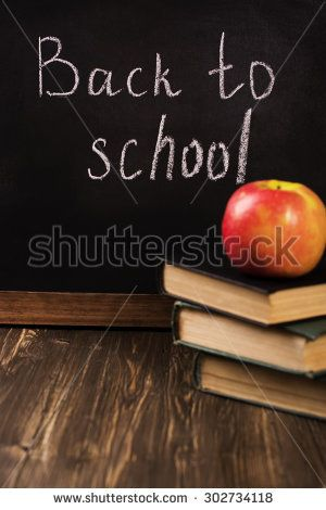 Back to school concept. Blackboard with a chalk, old books, apple and plastic letters. Vintage style. Selective focus