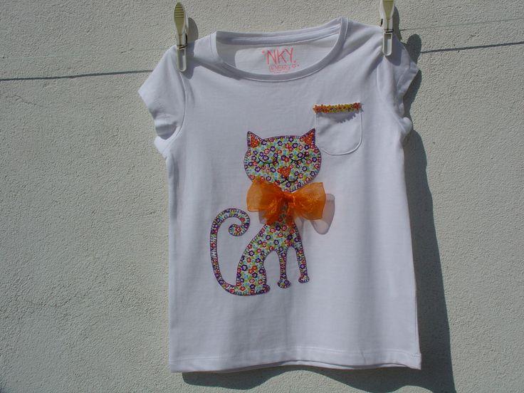 Camiseta blanca con gatito de aplicaciones patchwork en tonos naranjas y morados, con lazo naranja.