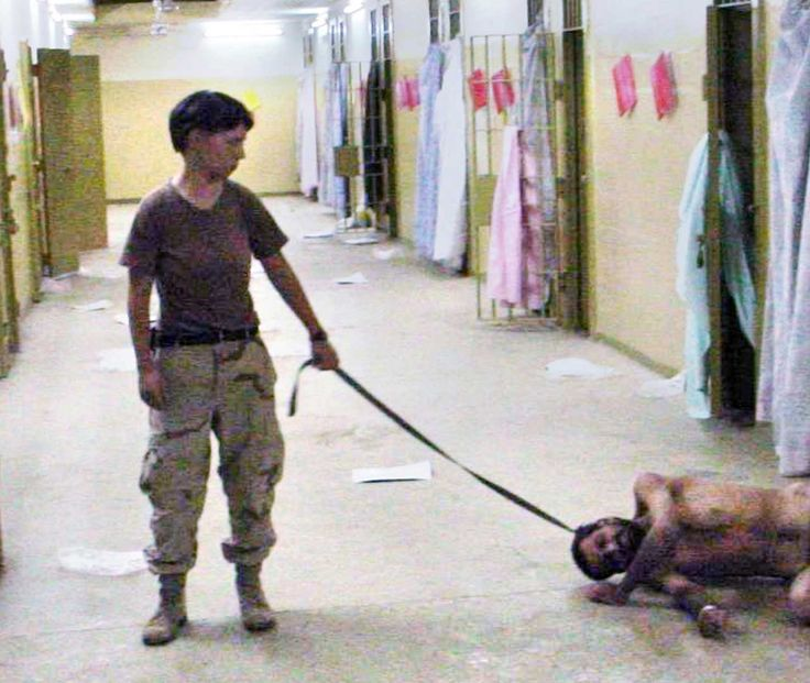 A photo obtained by the Washington Post and released May 6, 2004, shows U.S. Army Spc. Lynndie England, of the 372nd Military Police Company, with a naked detainee at the Abu Ghraib prison in Baghdad, date unknown