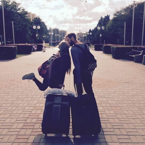 pareja de novios con maletas caminando por la calle