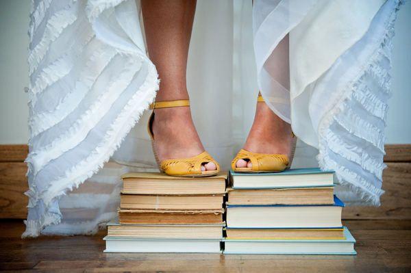 Unique wedding photo idea - the bride standing atop a stack of books!