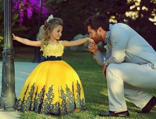 papa besando la mano a una niña vestida de princesa
