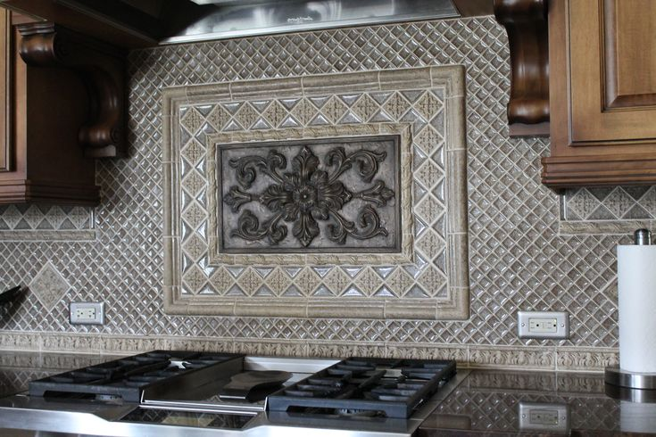 kitchen backsplash with bronze medallion and silver glass
