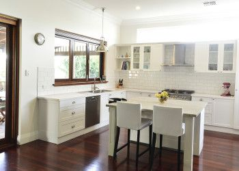 Character home renovation in North Perth featuring a classic white kitchen with jarrah floorboards, subway tiles, stainless steel appliances and a garden outlook.