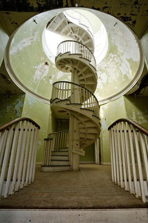 Wooden spiral staircase in the 1828 Administration Building in the abandoned insane asylum in Staunton, Virginia