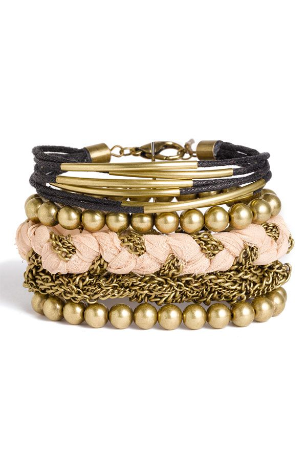 An eclectic collection of strands fashions a wide bracelet that mixes chain, beads, cord and braided fabric.