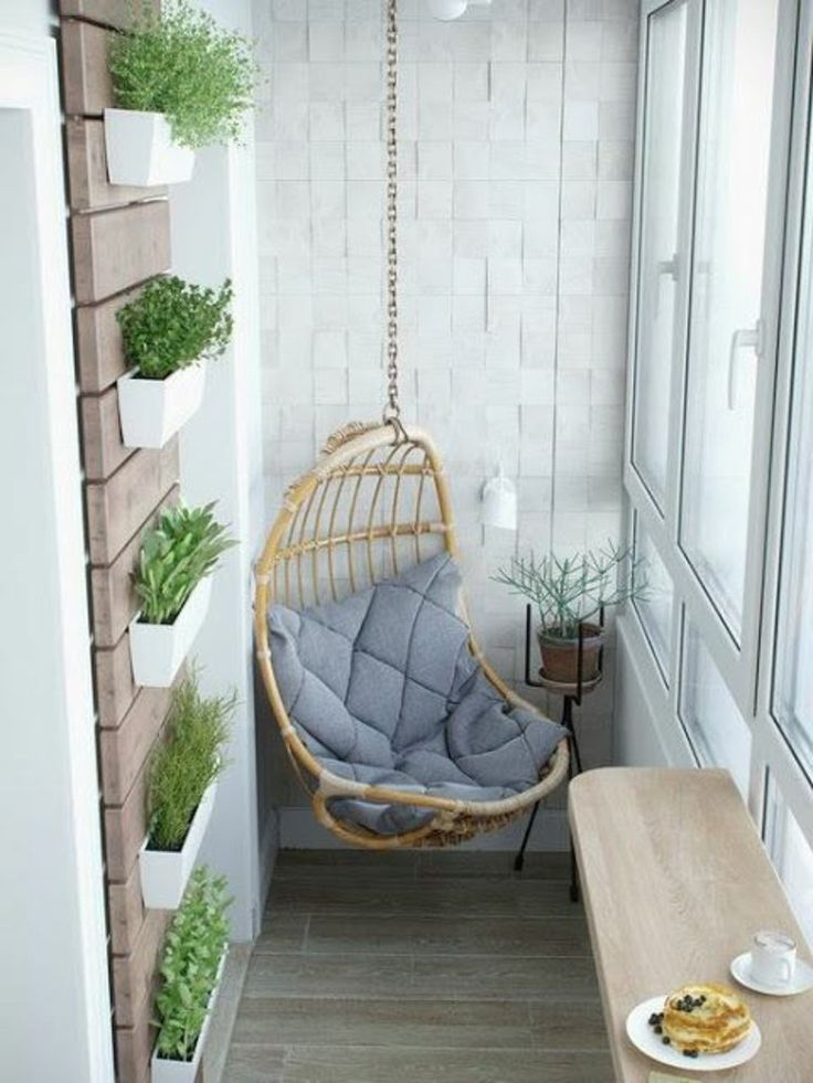 Hängekorbsessel und vertikaler Garten auf dem kleinen Balkon