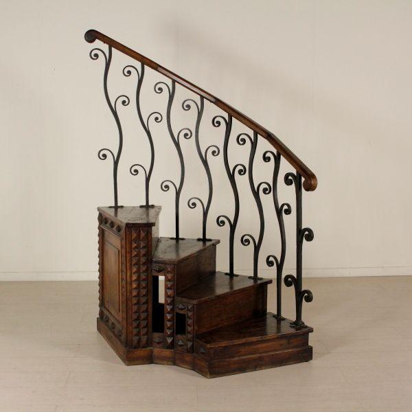 Scala a quattro gradini con bugnature. Ringhiera in ferro battuto con corrimano in rovere.