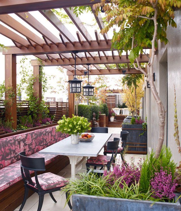 Chinoiserie deck boasts pergola over built-in bench adorned with fuchsia toile fabric cushions facing concrete top trestle table
