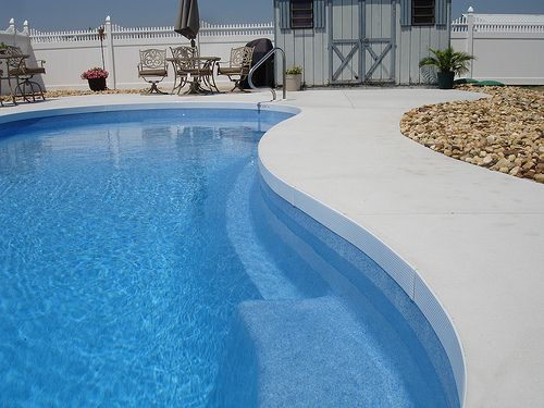 plain concrete patio around pool.  Clean lines, solid surface, not slippery, not pokey on your feet, light color so it's not so hot.