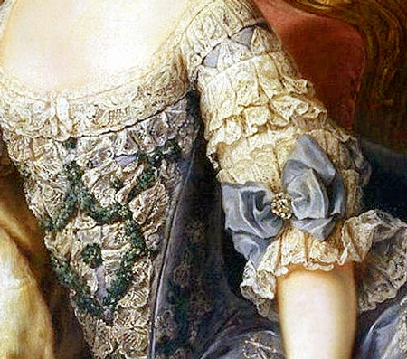low scooped neckline to bodice with intricate lace trim; stomacher of cream lace and green embroidery; tiered lace sleeve with large blue silk bow with diamond ornament center ending in lace flounce, bow matching color of blue brocade silk gown. Detail of 12 year old Archduchess Maria Antonia of Austria (Marie Antoinette).