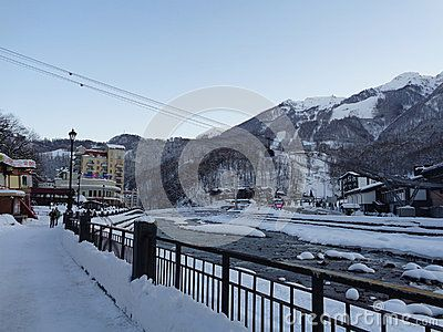 People walk along snow embankment, cableway over the river, high mountains with ski slopes