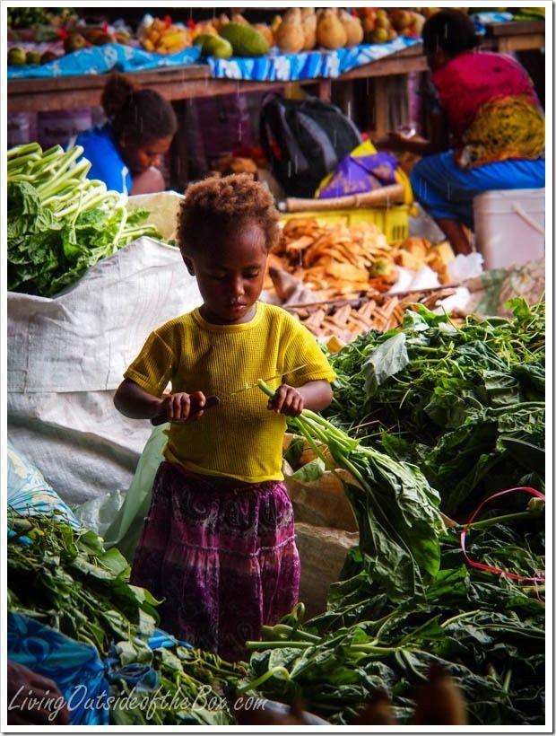 Toddler cuts greens with Mom at market in Port Vila, Vanuatu