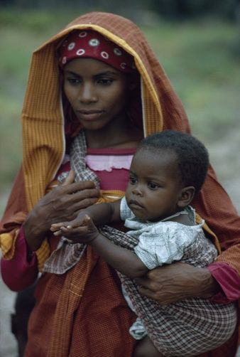 Africa | A young woman holds her young child. Mozambique