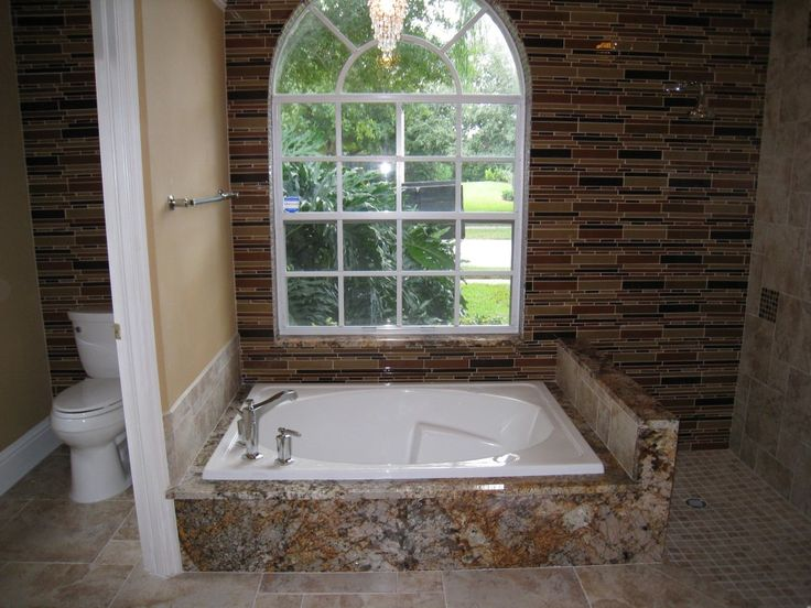 This isn't your standard shower/tub combo... a clever mixture of tile creates a unique space by the Home Improvement Source