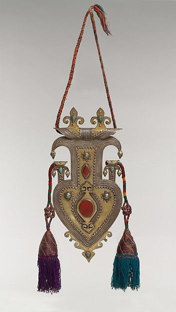 Cordiform pendant with tassles.Date: late 19th–early 20th century. Geography: Central Asia. Culture: Islamic. Medium: Silver, fire-gilded, with silver shot, decorative wire, cabochon and table-cut carnelians, slightly domed turquoises, and wool tassels.