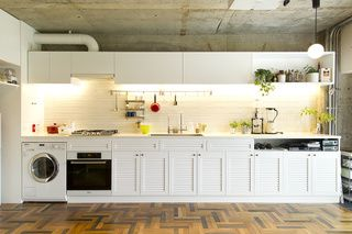 できるだけカウンタートップを広く長く取ることで、食材を広げて楽に調理可能。白い家具のような雰囲気に、カラーのキッチンツールが映える。