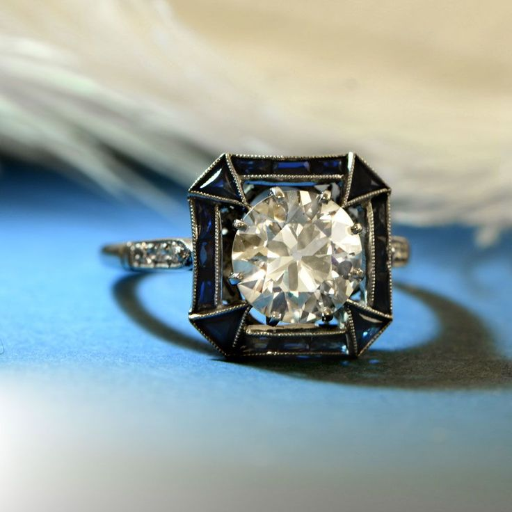 A French-cut sapphire frame surrounding a lively old European  cut diamond.