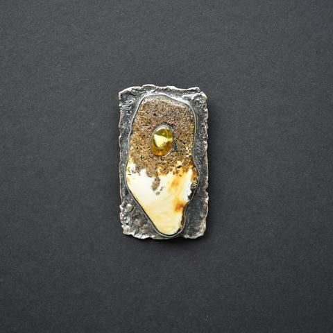 Amber pendant of white and black colors in silver setting