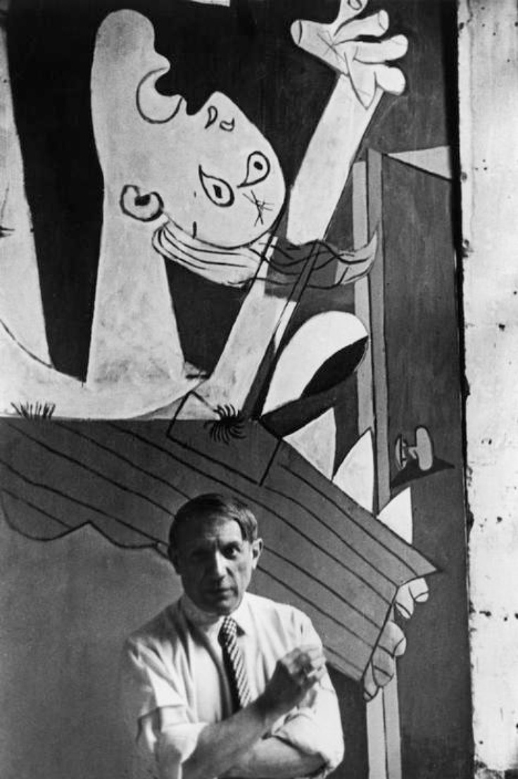 "Pablo Picasso in front of his painting ""Guernica"", at its unveiling at the Spanish Pavilion of the International World Fair held six weeks after the aerial bombing of the Basque village of Guernica."