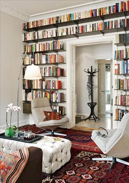 """Förvara stilfullt - Sköna hem  """"Ett platsanpassat hyllsystem runt dörren utnyttjar den knepiga ytan och gör rummet ombonat. Hyllplanen är täcksidor från Ikeas köksinredning, som sågats av. Konsolerna och väggskenorna sitter på 60 centimeters bredd, är det för långt emellan kan hyllorna bågna. Ett prisvärt sätt att skräddarsy bokhyllan runt dörrar, fönster, säng, som också ser välarbetat ut."""""""