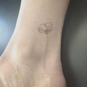 Tatuaje de una amapola de estilo fine line en el interior del...