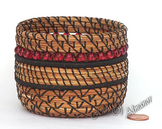 Ruby This pine needle basket is made with natural pine needles, gathered from the shores of Lake Almanor CA. Made with black thread and red glass beads. Coiled together to make a nice small unique basket, perfect for gift giving. This size fits nicely on a desk, bedside table or shelf;