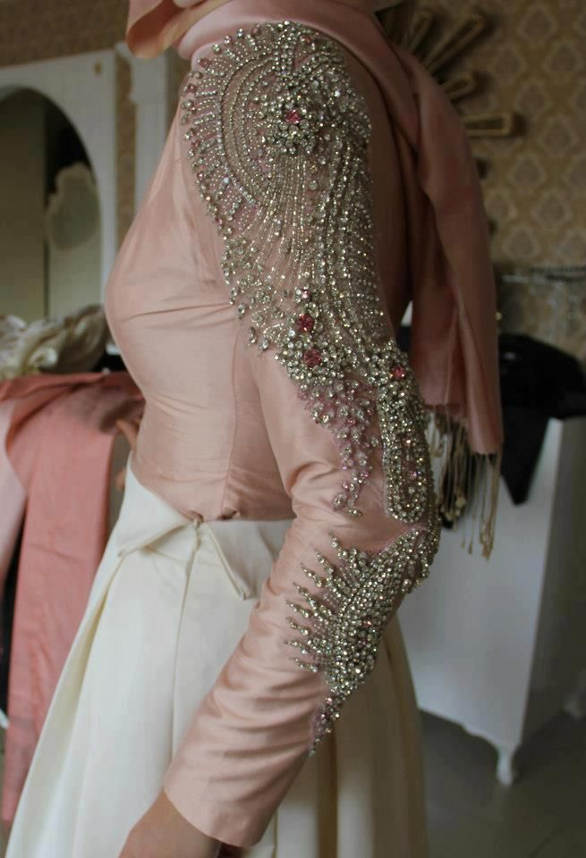 Photo detail of pale pink sleeve of tight fitting blouse, beaded in silver, tucked into long white skirt
