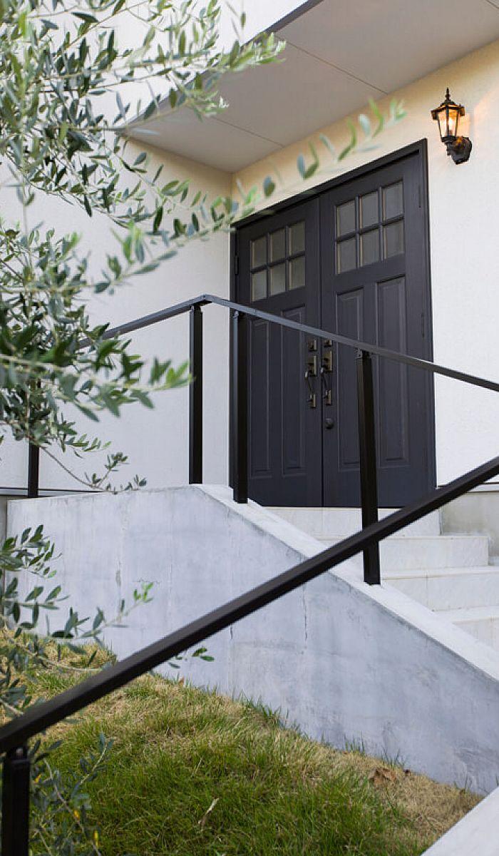 アプローチの階段の先に迎える玄関ドアも 海外の住宅を髣髴とさせる