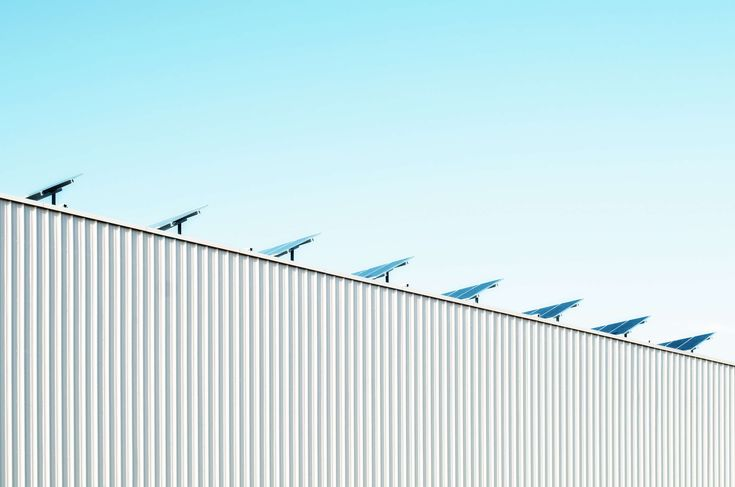 #airplane #architecture #blue sky #building #business #city #corrogated steel wall #electricity #green architecture #high #industry #lines #modern #outdoors #power #roof #solar #solar panels #steel structure #struct