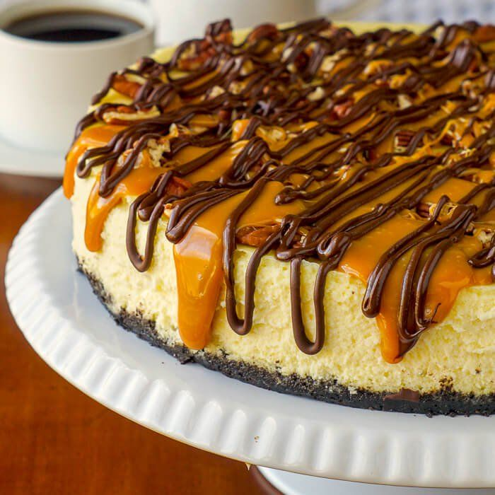 Turtle Cheesecake - a creamy vanilla cheesecake sits on a chocolate cookie crumb base topped with toasted pecans, gooey caramel & chocolate; pure decadence!