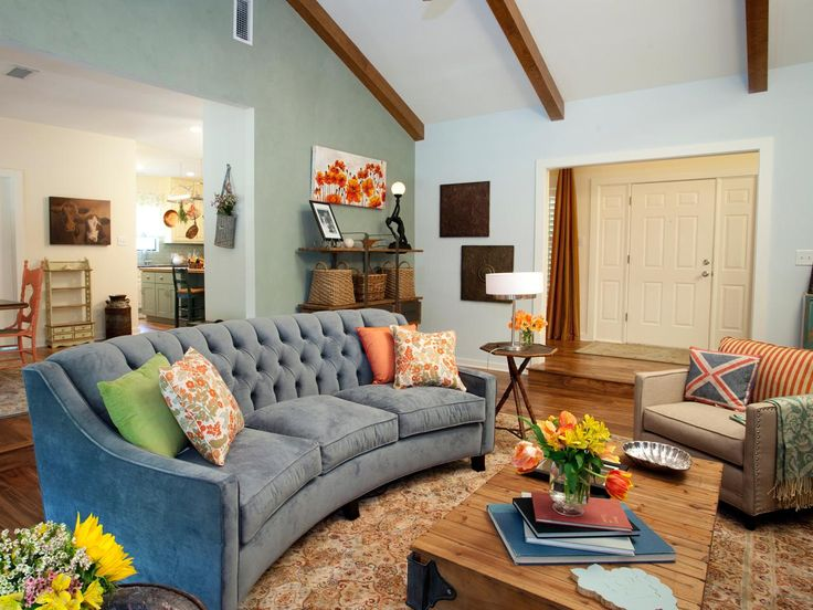 A blue sofa and floral-patterned throw pillows are bright and cheerful additions to this eclectic living room with exposed beams, as seen on HGTV's Property Brothers.