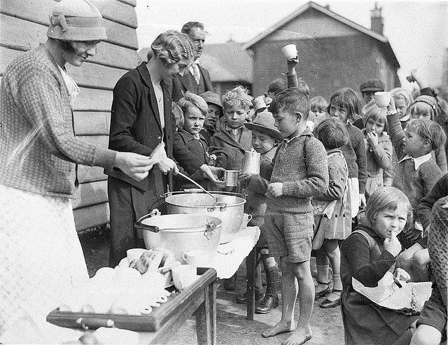 Schoolchildren line up for free issue of soup and a slice of bread in the Depression, Belmore North Public School, Sydney, 2 August 1934 / Sam Hood by State Library of New South Wales collection, via Flickr