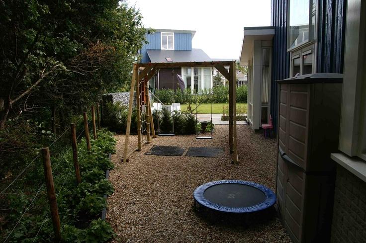 Naast het huis is er een speciale speelhoek voor de kinderen met een speeltoestel en trampoline.  De bodem is bedekt met een laag schelpen. Ontwerp en aanleg door hoveniersbedrijf van Elsäcker Tuin