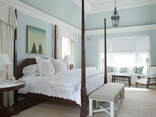 Blue walls, White bedding on traditional four poster bed.