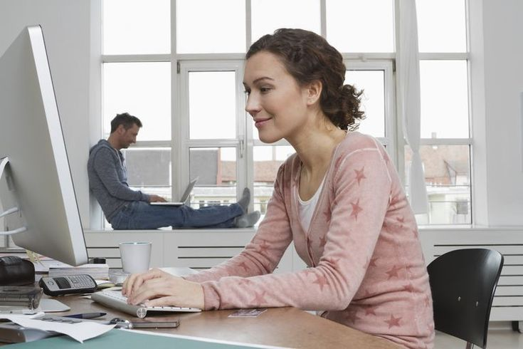 Woman at desk with man in background