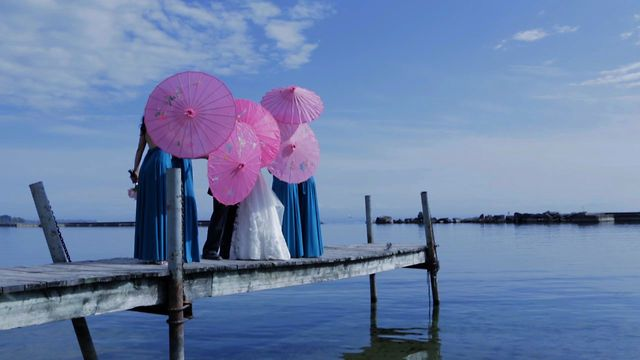 Loving those beautiful bright pink umbrellas against the bright blue sky - what a perfect day for a perfect wedding! Gorgeous decor and details in this one! (www.henjofilms.com)