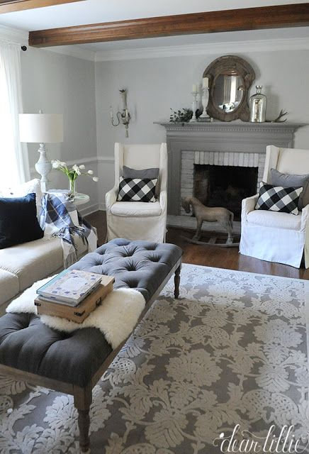 Adding touches like this plaid throw and velvet pillows like these ones from HomeGoods help add a cozy and warm touch to this gray and white family room with the gray fireplace mantel. (sponsored pin)